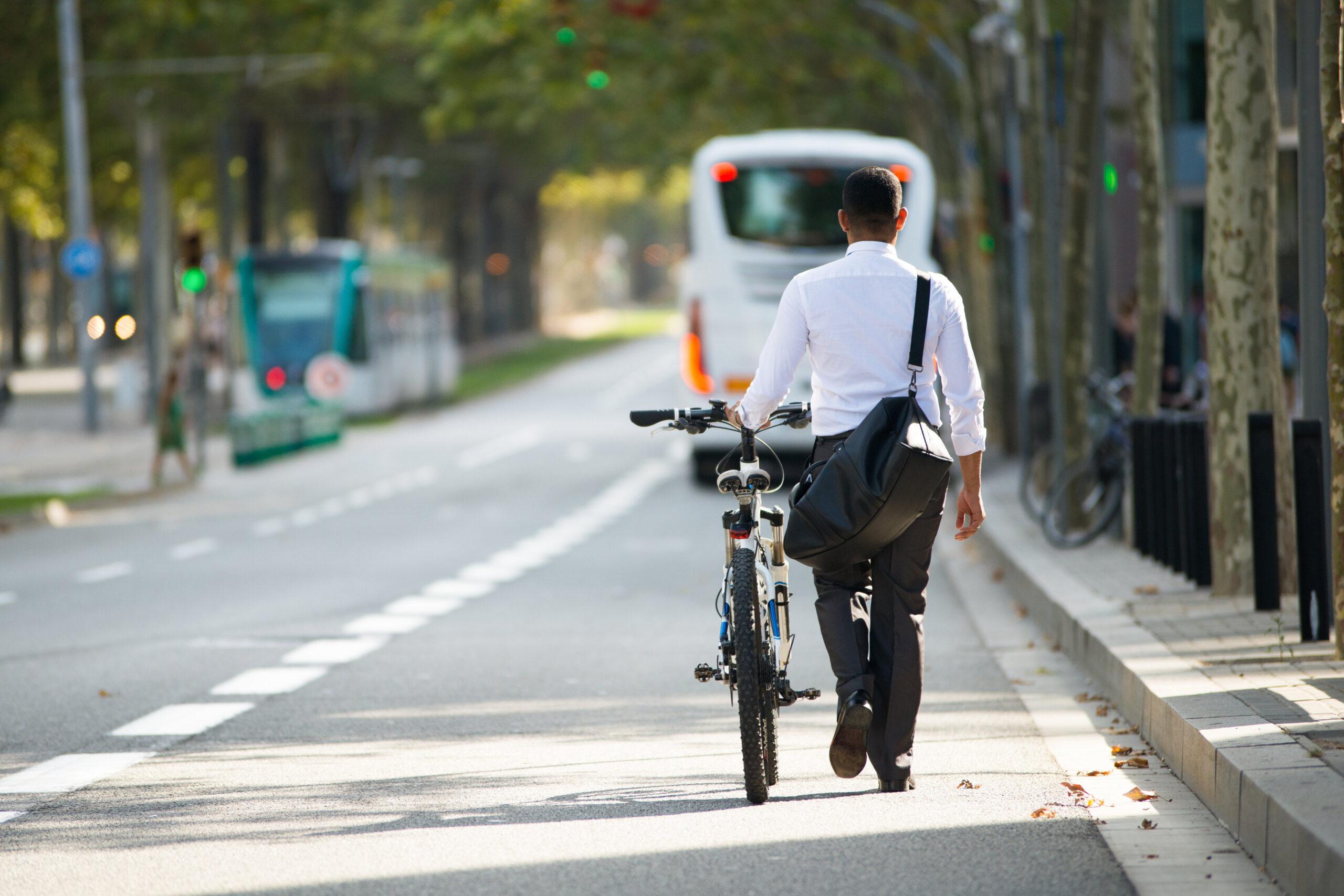 businessman walking with bike on street